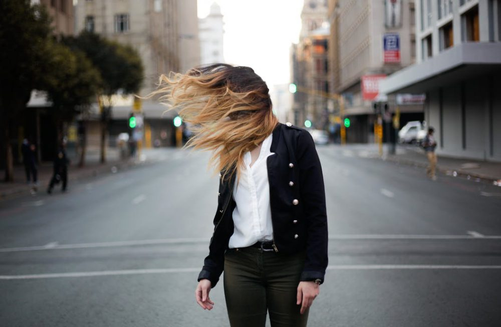 woman with long hair standing on road