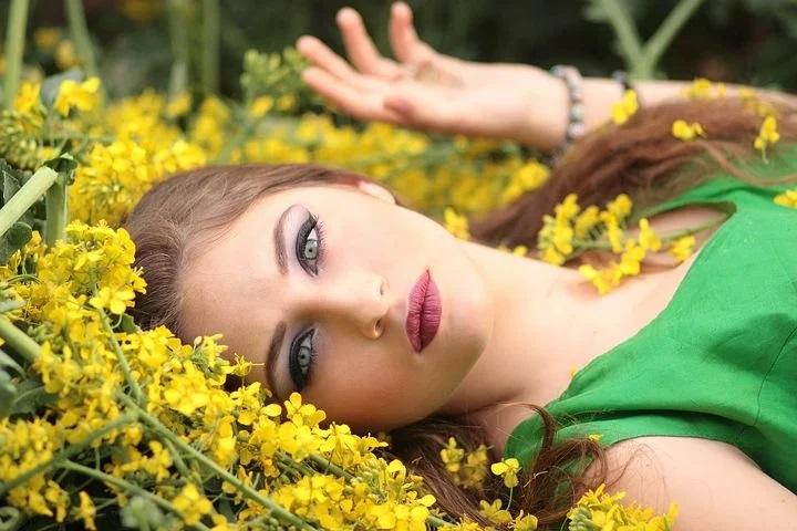young woman in makeup; sunflower; green dress; beauty